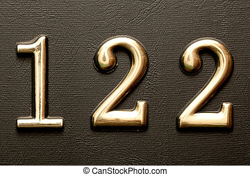 Brass door number 122 on the dark leather background - Close...