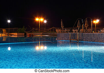 Night pool with lanterns, cafe and chairs near edge pool,...