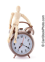 Wooden dummy sitting on old-styled metal alarm clock.