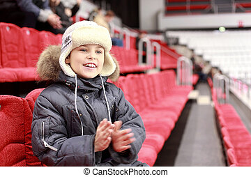 Boy with delight claps ones hands on hockey match