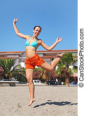young beauty woman jumping on beach and smiling, house and...