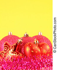 Top of three red Christmas tree balls behind star and heart...