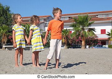 little boy and two girls standing on beach, holding for...