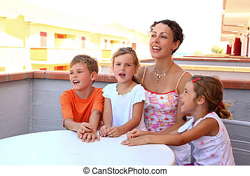 Mother and three children sit on verandah in summer near...