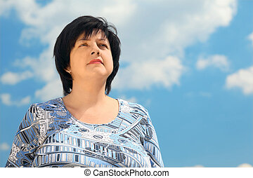 portrait of brunette plumpy mature serious woman, blue sky and clouds
