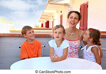 Two girls with boy and mother sit in day-time on balcony...