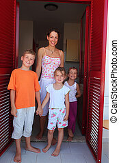 Mother with three children standing in doors from kitchen to balcony, holding hands
