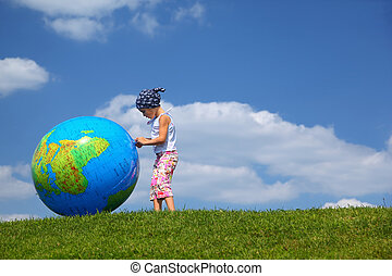Girl stands on  grass in  day-time and plays with an inflatable globe