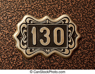 Door number 130 on the brushed metal background. - Close up...