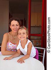 Mother with daughter sit on verandah near kitchen round...