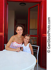 Mother with daughter sit on verandah round table and hold on...