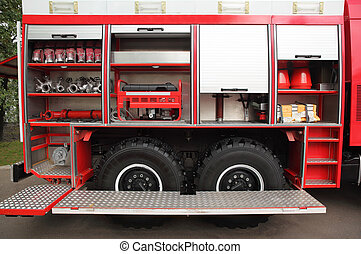 Open big red fire engine equipped with fire cocks and hoses...
