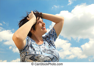 brunette plumpy mature woman smiling, hands on head, looking at side, blue sky and clouds