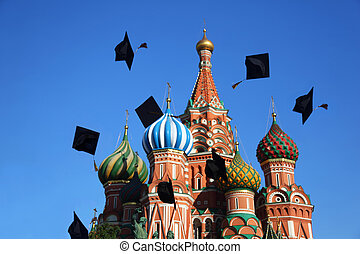 Black hats of graduation throw  in sky near St. Basil Cathedral. Moscow.