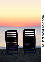 Two empty chairs stand on sand near  sea  during sunset