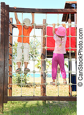 little boy and girl climbing on rope ladder at playground,...