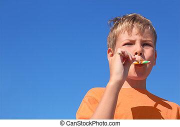 little boy in orange shirt eating multicolored lollipop,...