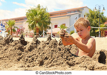 Boy on  beach sits and models hills from wet sand