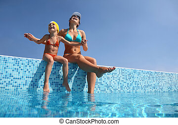 Mother with daughter sit on  parapet of pool and gladly lift  head to sky