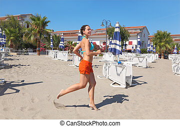 young woman smiling and running on beach near lounges and...