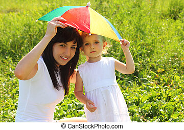 Mother and daughter hide under an umbrella from the sun