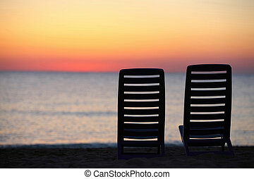 In evening at seaside two plastic chairs cost in evening...