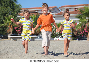 little boy and two girls walking on beach, holding for...