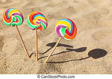 three multicolored lollipops sticked in sand on beach, sunny