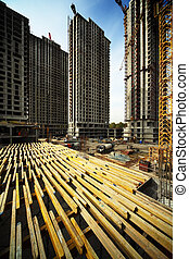 On wood planking between tall buildings under construction...