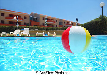 An inflatable ball lies in pool under open-skies near...