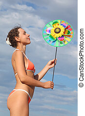 young beauty woman in orange bikini standing and holding...