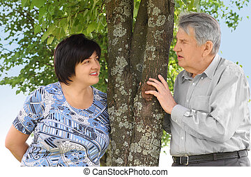 old senior and his adult daughter standing near tree, looking to each other, summer
