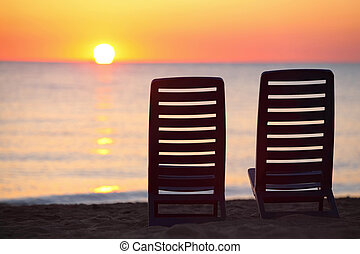 Two empty dark blue chairs stand on beach in evening with...