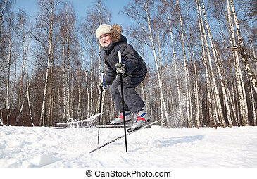 Young boy jumps sideways with cross-country skis and poles...