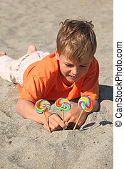 caucasian boy in orange shirt lying on beach, multicolored...