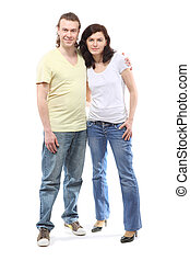 Young couple in jeans, boy and girl, are standing in embrace and smile