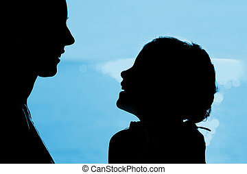 Mother with daughter silhouette near sea, opposite each other, laughing