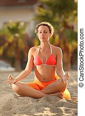 young woman in orange bikini sitting on beach in lotus pose...
