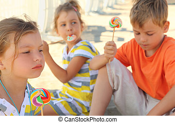 serious children sitting on beach and eating lollipops,...