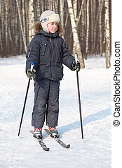 Young boy stands on cross-country skis and looking to side...