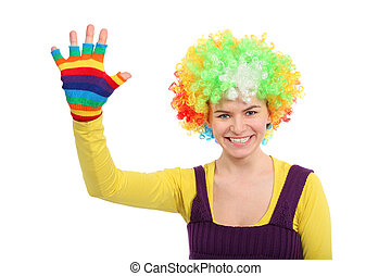 Funny girl in colored curly wig shows hand in multicolor glove
