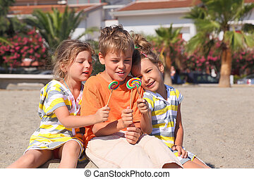 little boy and two girls sitting on beach and holding...