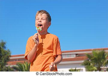 little boy in orange shirt licking multicolored lollipop,...