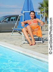 young woman in orange bikini and pareo sitting on beach chair near pool and smiling