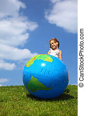 Girl stands on grass and looks aside next to an inflatable...