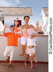 Mother with girl and boy stand on balcony on one leg and...