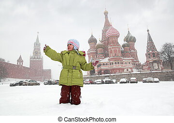 Little girl catches snowflakes in front of background St. Basil's Cathedral in Moscow, Russia at wintertime during snowfall