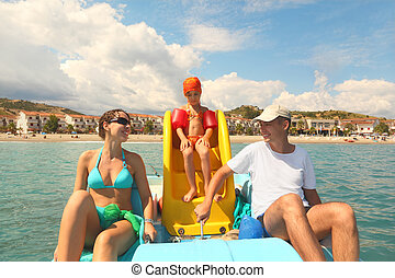 family with girl on pedal boat with yellow slide in sea,...