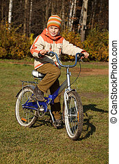 Boy on bicycle in autumn park on sunny day. He was wearing...