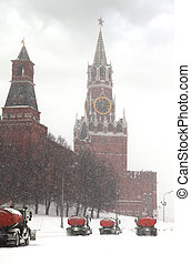 Column of snow-remover trucks on the road near Kremlin chiming clock of the Spasskaya Tower in Moscow, Russia at wintertime during snowfall